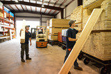 Brandon Cuddy and Andre Paquet inspect and sort lumber in the new lumber storage building at Hook's.