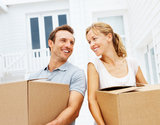 Happy mature man and woman with boxes moving in new house