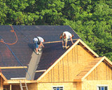 New large home being constructed in new neighborhood, men installing tar paper gettind ready for shingles