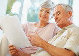 Charming senior man and woman reading documents at their house