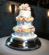 Three colours of avalanche roses between the tiers of a wedding cake