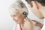 Mature male doctor examining patient's ear using otoscope in clinic