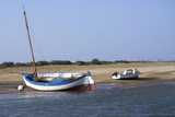 Two boats one motor the other a traditional sailing craft moored at low tide on an estuary