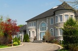 Front of a large beautiful executive home under blue sky