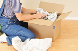 Woman unpacking moving box in an empty room