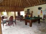 The communal area, pool table, TV, games, darts, tables, all under the palapa roof,