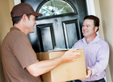 Man receiving a package delivery from a courier at his home.   Removal Companies Dulwich Ltd. 16 Grove Vale