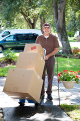 Delivery man or mover bringing boxes up your front walk.