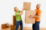 Middle-aged man holding cardboard moving boxes while woman places one on stack.