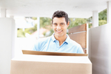 Happy young man with box moving into new home smiling