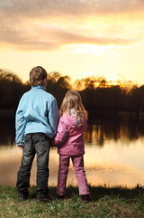 Little girl in pink clothes and boy in blue jacket standing back on bank of river and admire on sunset