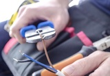 Closeup of worker's hands cutting electric wires with pliers.