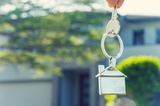 Hand holding a house key in front of a large house. The keyring has a house shaped icon on the end and is shiny silver colour. The house has a tree in front of it. The keyring house icon is dangling down. Close up with shallow focus. New house concept.