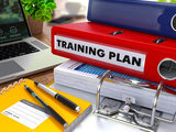 Red Ring Binder with Inscription Training Plan on Background of Working Table with Office Supplies, Laptop, Reports. Toned Illustration. Business Concept on Blurred Background.