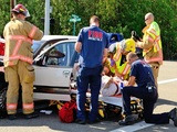 Roseburg, OR, USA - August 27, 2013: Fire fighters and paramedic EMT personnel extricate the victim of a two vehicle head on accident at an intersection in Roseburg, OR on August 27, 2013