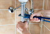 hands of a plumber with sink and wrench Hays Cooling Heating & Plumbing 24825 N 16th Ave #115