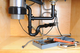 Detail of the plumbing system under a modern kitchen sink, with a plumbers tool tray and equipment. Horizontal format., Hays Cooling Heating & Plumbing, Phoenix