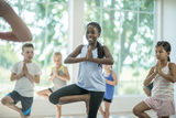 A multi-ethnic group of elementary age children are taking a yoga class together. They are standing in tree pose and balancing on one foot.