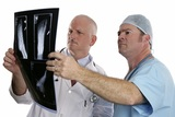 Two doctors examing the xray of a foot.  (focus on young doctor in foreground)