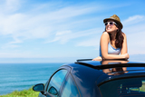 Relaxed happy woman on summer travel vacation to the coast leaning out car sunroof with the sea on background. ** Note: Shallow depth of field