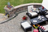 Brick paved patio with comfortable patio furniture with modern armchairs and a stool around a table set with tea and cookies alongside a low curving wall overlooking a green lawn, high angle view
