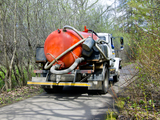 Orange sewage septic tank on truck in the countryside