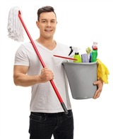 Young man holding a bucket full of cleaning products and a mop isolated on white background