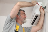 Electrician installing electrical plug for air conditioner