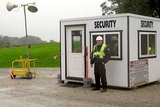 Security guard at booth guarding construction site from unwanted visitors.