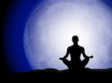 Person meditating in front of the full moon