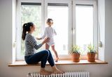 Beautiful young mother sitting on window sill with her cute little daughter looking out of window Sunstopper Window Tinting 2544 South Harbor City Boulevard