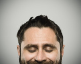Portrait of a real caucasian young man with happy expression and eyes closed. Brown eyes and hair with beard. 35 years old north american. Horizontal color image from a dslr camera in studio.