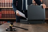 50245697 - midsection of lawyer putting documents in briefcase with gavel at desk in courtroom