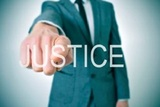 27500695 - man wearing a suit pointing the finger to the word justice written in the foreground