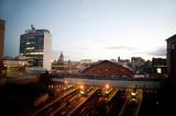 High angle view of Glasgow Queenstreet Station at night with four illuminated trains waiting for passengers at the covered platforms and a view over the rooftops of the city beyond