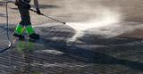 Wet cleaning of street with pressurized water.