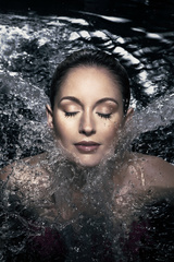 Caucasian woman in her 20's with eyes closed submerged to her neck in water