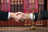 50278233 - justice scale on wooden table with judge and client shaking hands in background at courtroom