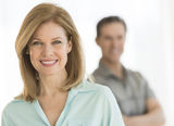Portrait of beautiful woman smiling with man standing in background at home