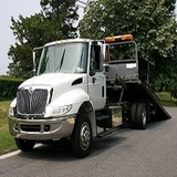 A white flatbed tow truck for towing & transporting cars & trucks