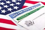 20947903 - united states of america social security and green card with us flag on the background  immigration concept  closeup with shallow depth of field