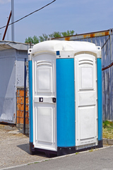 Portable toilet cabin at open construction site