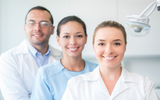 Portrait of a group of dentists smiling and looking at the camera - healthcare and medicine concepts