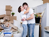 Happy young couple staying together in their new common flat and kissing