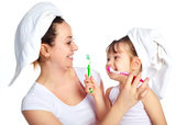 young beautiful mother and her little daughter brushing teeth and laughing