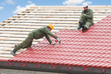 two workers on roof at works with metal tile and roofing iron