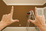 Hands Framing Brown Painted Room Wall Interior with Ladder, Paint Bucket and Rollers.