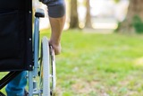 Male hand on wheel of wheelchair during walk in park