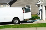 Generic professional carpet & upholstery cleaning service van with hoses coming out the back of the vehicle. Typical American residential subdivision background.