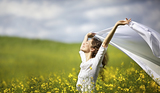 Young happy woman standing in yellow rapeseed field holding a white piece of cloth in the wind expressing freedom.